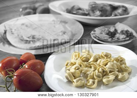 fresh tortellini with sauce of fresh tomatoes on a black and white background