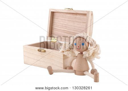 Horizontal front view of a wooden toy doll near an open chest on white background
