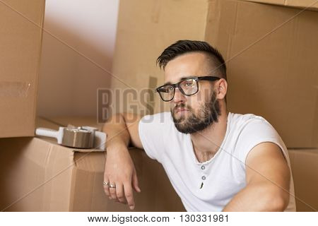 Young man moving in a new apartment sitting on the floor surrounded with cardboard boxes with packing machine placed on one of the boxes in the background