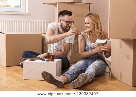 Couple in love sitting on the floor in their new apartment surrounded by cardboard boxes eating take out chinese food and drinking ice tea