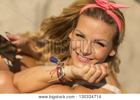 Portrait of a beautiful young blond sitting on a sunbed on a beach and enjoying the sun