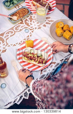 Close up of unrecognizable young woman holding striped plate with american hot dog and corn in outdoors summer party