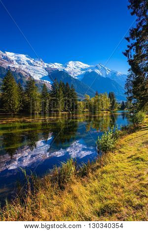 The lake reflected the snow-capped Alps and evergreen spruce. Early autumn in Chamonix, Haute-Savoie. France