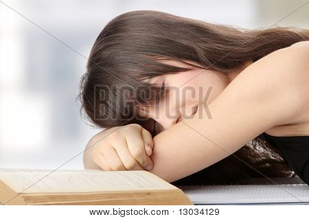 Sleeping while learning - tired teen woman sleeping on desk