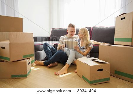 Couple using tablet in their new apartment