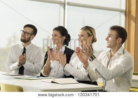 Four business people on a project presentation in a conference room applauding at the end