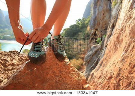 young woman rock climber tying shoelace at mountain rock