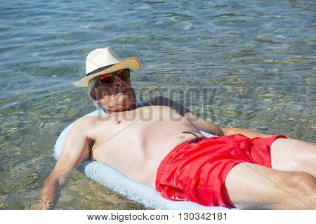 Retired man sleeping and floating on inflatable bed floating in the sea