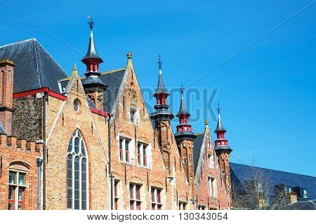 Traditional medieval brick house exterior against blue sky in Brugge, Belguimn with copy space