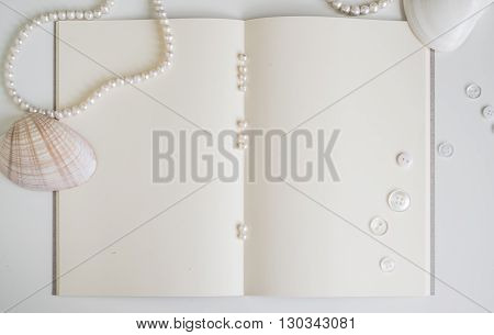 empty vintage book page with chic pearls and shell decoration background with copy space