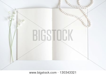 empty vintage book page with chic pearls decoration and lily of the valley background with copy space