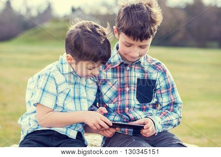 Little kids playing on tablet outdoor vintage style