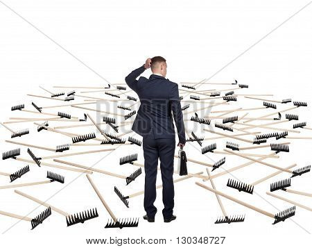 Young businessman in a suit and with a briefcase is undecided before the field that hosts a lot of rakes. He is afraid to move further. Concept of difficulty of deciding.
