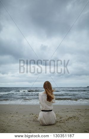 photo of young beautiful woman on cold windy beach
