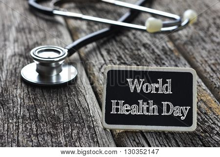 Medical Concept-World health Day word written on blackboard with Stethoscope on wood background