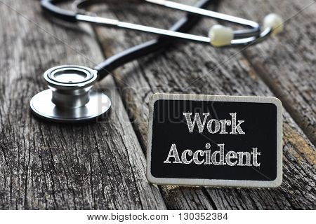 Medical Concept- Work Accident word written on blackboard with Stethoscope on wood background