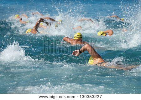 Swimming athletes in a triathlon contest in the sea