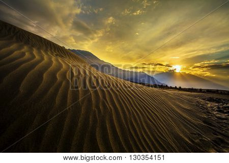 Sun rise at sand dunes against the background of distant colorful mountain range and sunrise sky, Ladakh, Himalaya, Jammu & Kashmir, Northern India