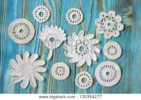 Vintage background with Irish cotton lace crochet flowers. Knitted background on emerald blue colored wooden background. Knitted frame with handmade lace. Christmas and Valentine's day background.