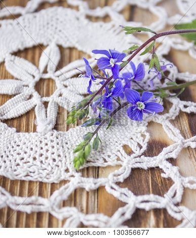 Blue flower on wooden table, rustic background. Crochet lace background
