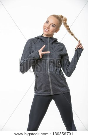 Beautiful blonde girl in the sportswear stands on the white background in the studio. She wears black-gray pants and gray hoody. She holds her right hand raised and shows V symbol. She holds her plait with left hand. She looks into the camera with a smile