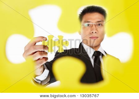 Businessman Holding The Last Piece Of Puzzle