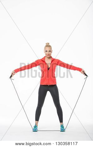 Beautiful blonde girl in the sportswear stands with skipping rope on the white background in the studio. She wears cyan-yellow sneakers, black pants, black t-shirt and red hoody. Her feet are on the skipping rope. She holds the skipping rope with separate