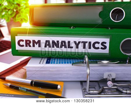 Green Ring Binder with Inscription CRM - Customer Relationship Management - Analytics on Blurred Background of Working Table with Office Supplies and Laptop. 3D Render.