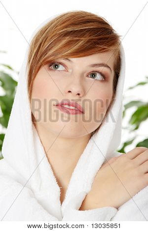 Young smiling blond teen woman wearing bathrobe. Green leafs in background