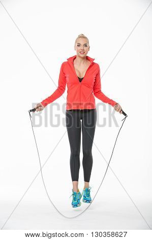Attractive blonde girl in the sportswear jumps with skipping rope on the white background in the studio. She wears cyan-yellow sneakers, black pants, black t-shirt and red hoody. Her feet are off the floor. She looks into the camera with a smile. Vertical