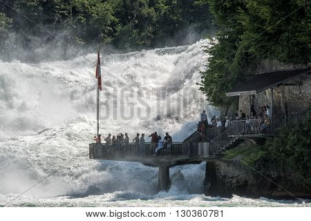 SCHAFFHAUSEN SWITZERLAND - 16 JULY 2015 - people observe majesty of rhine waterfalls really close to the water