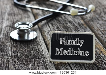 Medical Concept- Family Medicine word written on blackboard with Stethoscope on wood background