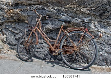 old rusted bycicle on rocks background detail