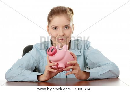 Young woman in blue shirt with pink piggy bank sitting behind the desk, isolated on white background