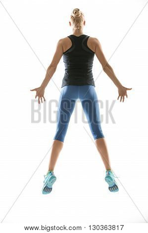 Sportive blonde girl in the sportswear jumps on the white background in the studio. She wears cyan-yellow sneakers, mint socks, blue pants and black sleeveless t-shirt. Her hands are on the sides of her torso, feet are off the floor. Photographed from the