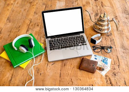 Laptop with white screen with earphones, smart watch, glasses, kettle books and money on the wooden table