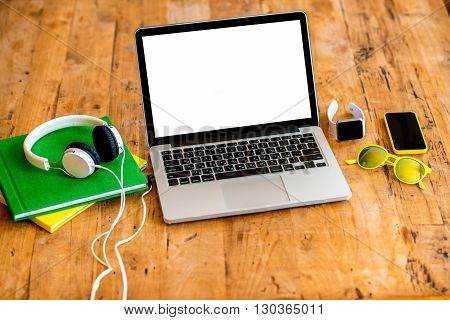 Laptop with white screen with earphones, smart watch, books, smart phone and glasses on the wooden table