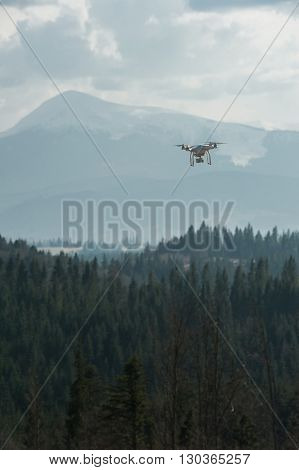 White drone with digital camera in dark sky over the mountains
