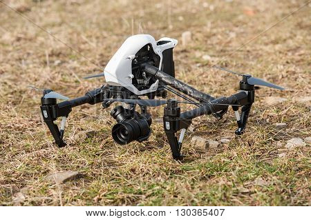 White drone quad copter with digital camera on ground.Selective focus