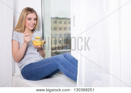 Portrait Of Young Woman Having Breakfast With Corn Flakes At Home