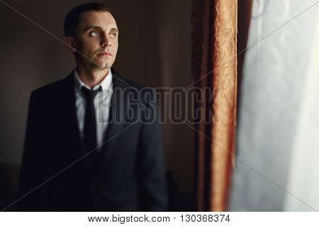 Handsome Stylish Happy Groom Posing Before Wedding Near Window