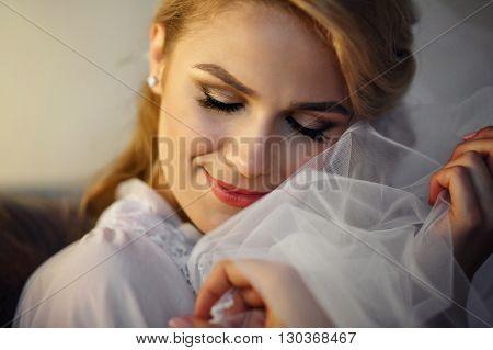 Beautiful Blonde Bride In Vintage Robe Posing On Sofa Closeup
