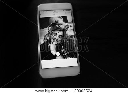 Two Golden Wedding Rings On Smartphone With Photo B&w