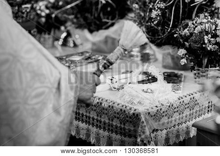 Priest & Wedding Rings Baptized With Holy Water At Ceremony B&w