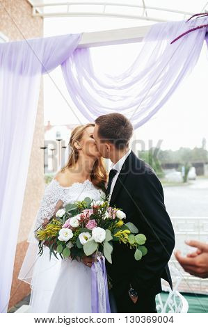 Romantic Happy Couple, Bride & Groom Kissing At Wedding Aisle