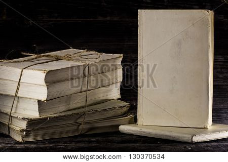 stacked books on a wooden background place for text