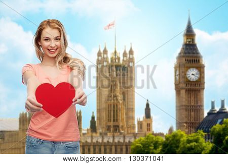 love, travel, tourism, valentines day and people concept - smiling young woman or teenage girl with blank red heart shape over big ben london and city background