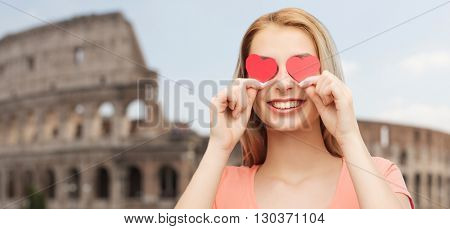 love, travel, tourism, valentines day and people concept - smiling young woman or teenage girl with red heart shapes on eyes over coliseum background