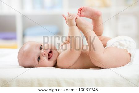 Funny little baby wearing a diaper playing on white bed in nursery room. Happy child after bath or shower. Infant kid diaper change and skin care. Smiling kid playing with his feet.