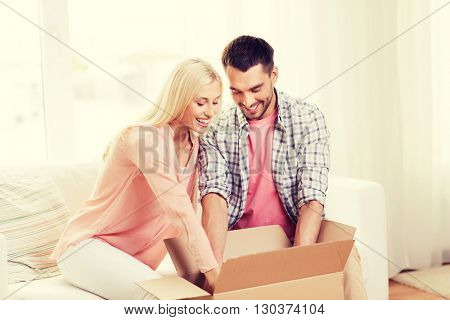 people, delivery, shipping and postal service concept - happy couple opening cardboard box or parcel at home